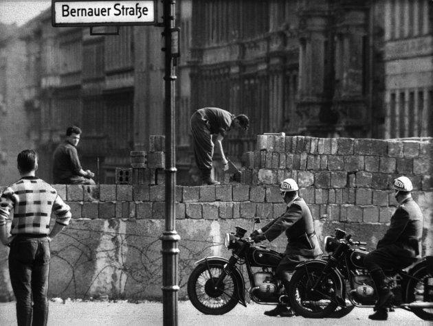「ベルリンの壁」を積み上げる東独の作業員(中央)。手前で見上げているのは西ベルリンの警官。撮影日:1961年06月02日