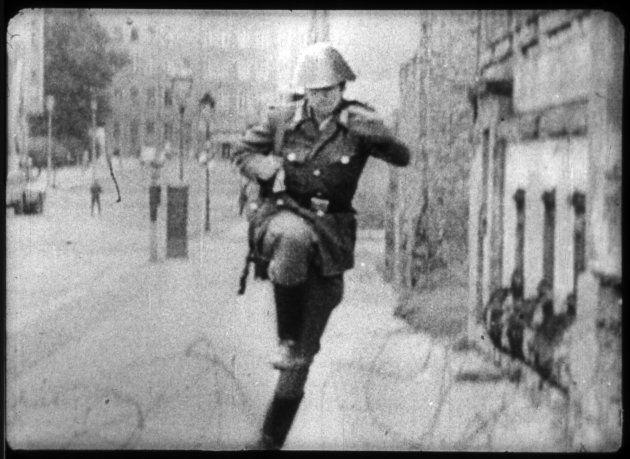 東ドイツ人民警察機動隊のコンラート・シューマン隊員。国境警備任務に就いていたが「ベルリンの壁」構築後、初の亡命者となった。彼が鉄条網を飛び越える姿を捉えた写真は「自由への跳躍」と題され、東西冷戦を象徴する写真の1つとなった。15.Aug.1961...