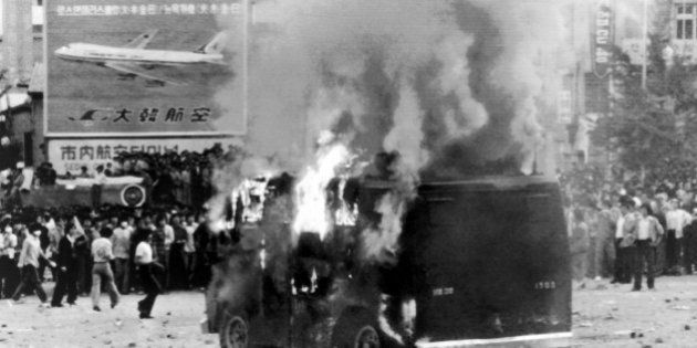 Student demonstrators watch a police vehicle burn near Seoul's South Gate on Thursday, May 15, 1980....