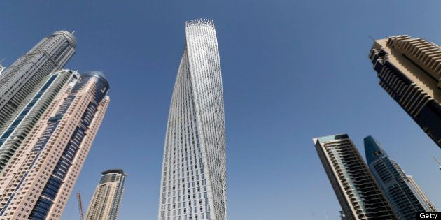 The Cayan tower (C), the world's tallest twisted tower stands at Dubai's Marina on June 11, 2013 in the...