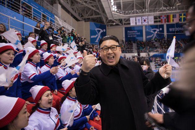 A man impersonating North Korean leader Kim Jong Un gestures as he stands before North Korean cheerleaders...