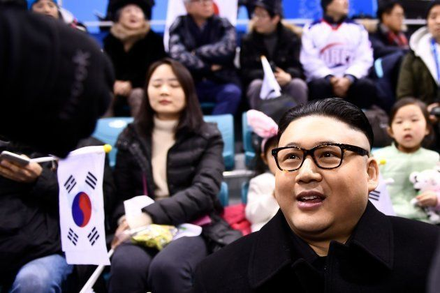 A Kim Jong Un impersonator sits with spectators during the final period of the women's preliminary round...
