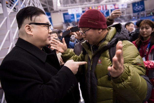 A Kim Jong Un impersonator is confronted during the final period of the women's preliminary round ice...