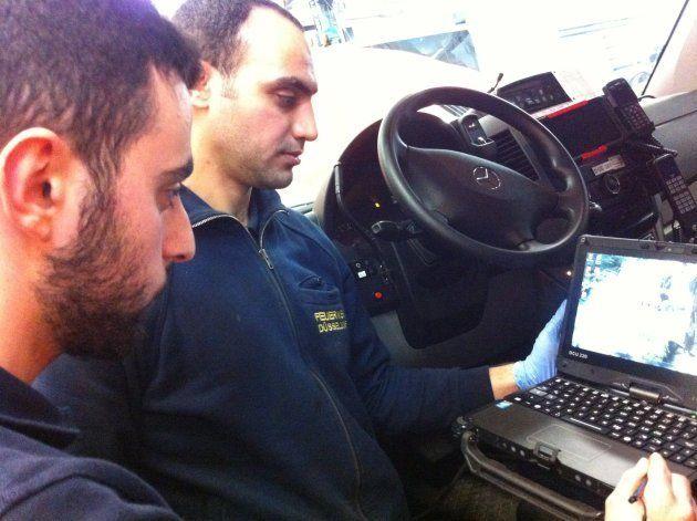 整備工場の職業訓練生、ヘガップさん(左)とアル=ハムベさん(右)。小型トラックにノートパソコンを接続して、車両の状態をチェックする。