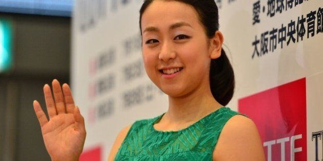 Japan's figure skating world champion Mao Asada waves after a press conference for the upcoming ice show...