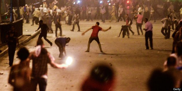 Ousted president Mohammed Morsi supporters and anti Morsi protesters hurl stones at each other as they...