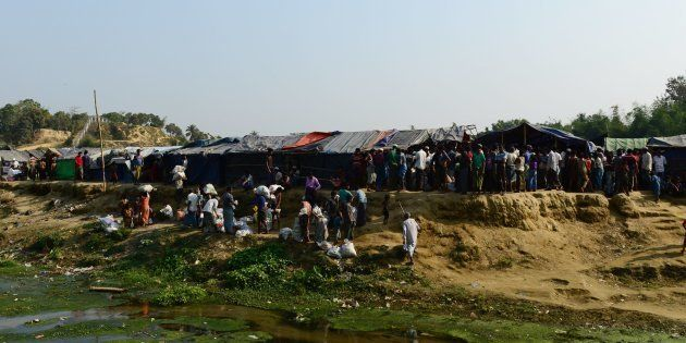 Rohingya refugees collect relief material next to a settlement near the 'no man's land' area between...