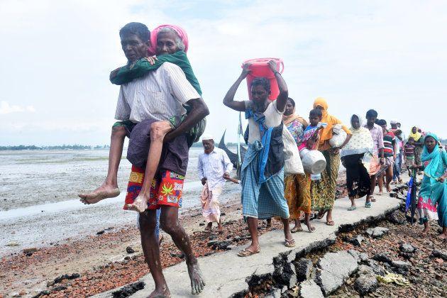 ミャンマーから逃れ、バングラディシュとの国境を越えて進むロヒンギャの人たち=2017年9月