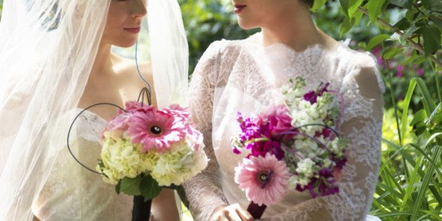 Horizontal outdoor garden shot of two young women in wedding dresses with bridal bouquets gazing into...