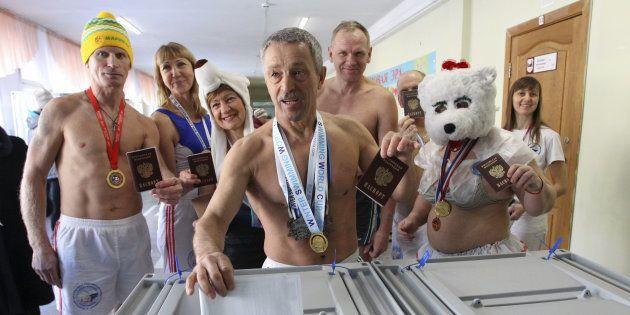 コスプレ姿や上半身裸のまま投票する寒中水泳クラブのメンバー。メンバーらは投票所の前で組体操のパフォーマンスも披露した=3月18日、ロシア中部のバルナウル