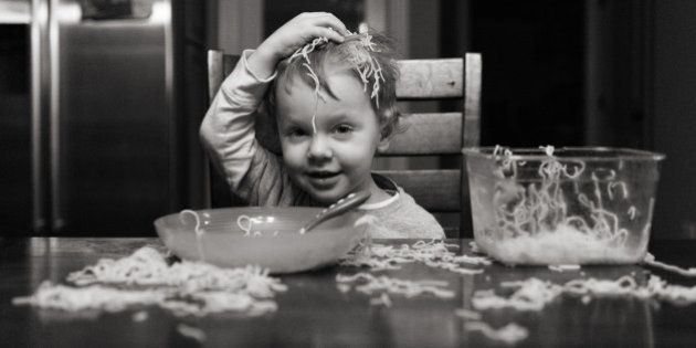 Silly toddler putting spaghetti on head at messy table