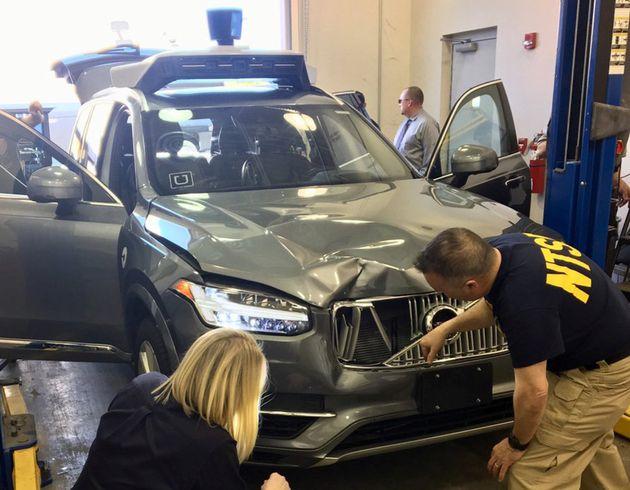National Transportation Safety Board (NTSB) investigators examine a self-driving Uber vehicle involved...