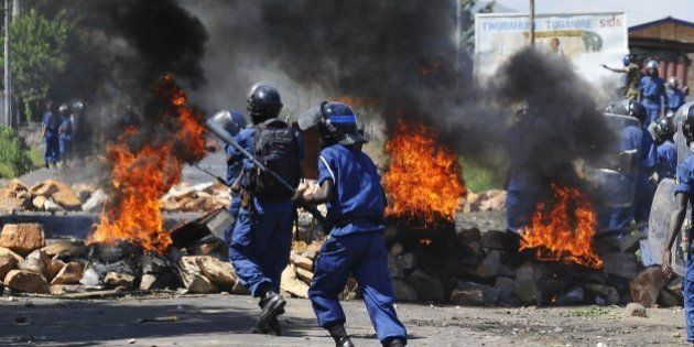 Burundian riot police run past a tire fire during a protest against the president's bid to cling to power...