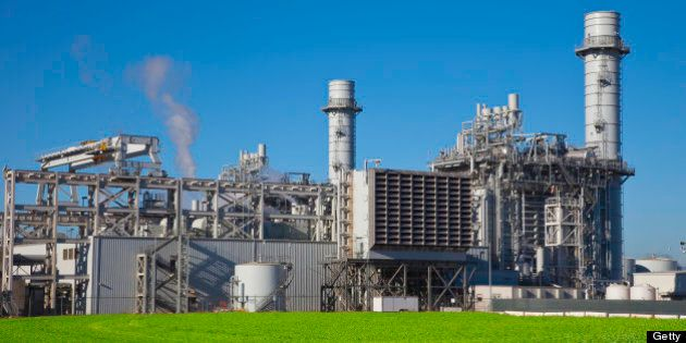Natural gas fired turbine power plant with it's cooling towers rising into a blue