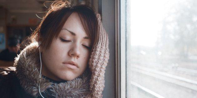 Portrait of sleeping girl, listening to music on headphones. Beautiful brunette in warm clothing