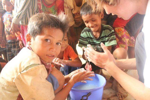 カンボジアで子供と手洗いをする荒井