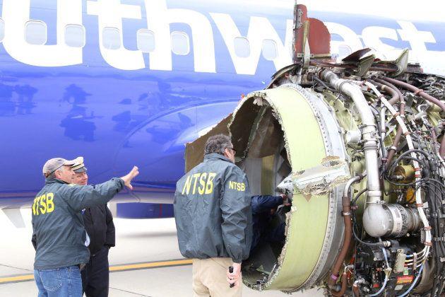 破損したエンジンを調査する国家運輸安全委員会(NTSB)の職員