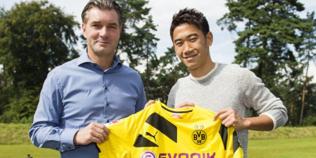 DORTMUND, GERMANY - AUGUST 31: (EXCLUSIVE COVERAGE) New signing Shinji Kagawa (L) of Dortmund poses with...