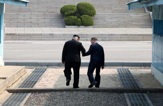 手をつないだまま軍事境界線を越え、北朝鮮側に入る金正恩氏(左)と文在寅氏=板門店