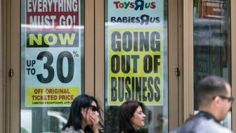 Pedestrians pass in front of a 'Going Out Of Business' sign displayed outside a Toys 'R' Us retail store at Times Square in New York, U.S., on Friday, May 11, 2018. As playtime ends for Toys 'R' Us, customers are being invited to attend the bankrupt company's final sales and snap nostalgic selfies with a Geoffrey the Giraffe banner and the #alwaysatrukid hashtag. Photographer: Jeenah Moon/Bloomberg via Getty Images