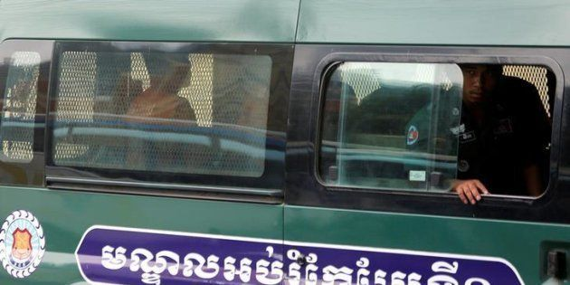 Uon Chhin and Yeang Sothearin, former journalists of the Radio Free Asia (RFA), sit inside a police vehicle...