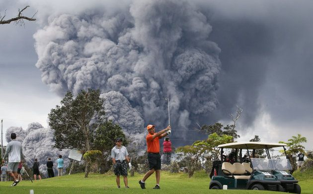 HAWAII VOLCANOES NATIONAL PARK, HI - MAY 15: People play golf as an ash plume rises in the distance from...