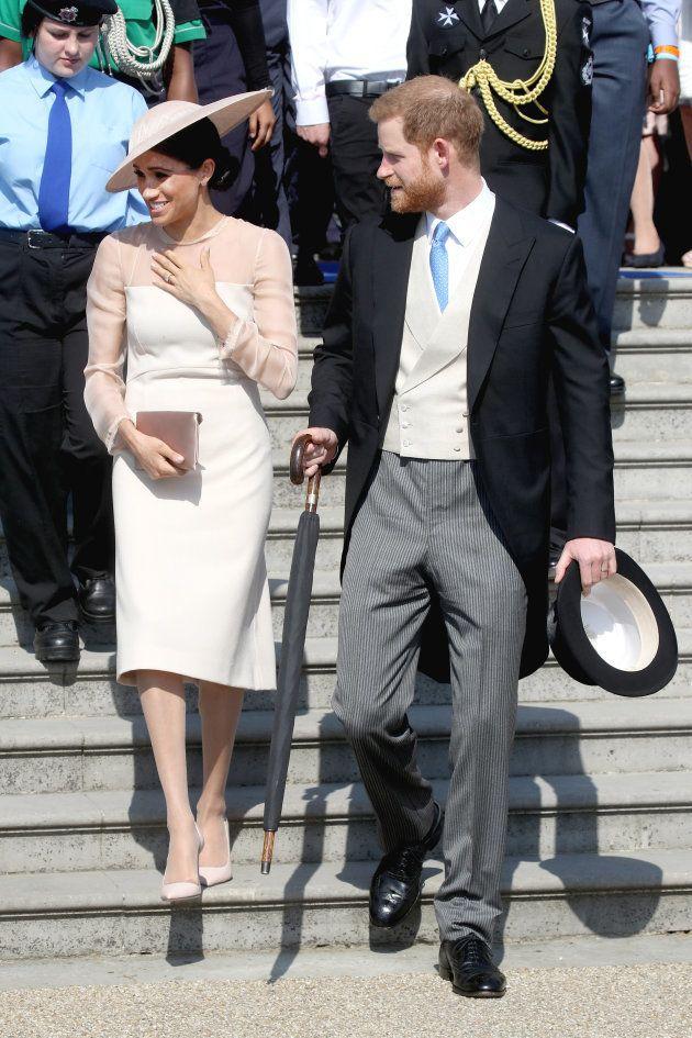 園遊会に出席したヘンリー王子(右)とメーガン妃(左)=22日、ロンドン、バッキンガム宮殿