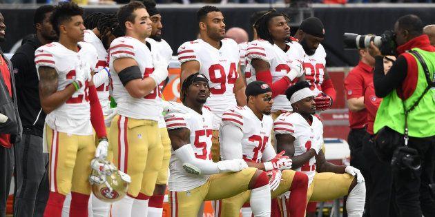 国歌斉唱中に片膝をついて起立を拒否するサンフランシスコ・49ersの選手ら=2017年10月、テキサス州ヒューストン