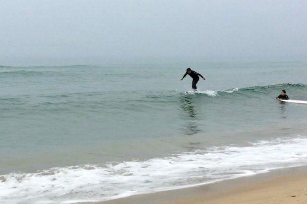 日本海(韓国名:東海)で波に乗るサーファー=5月29日、韓国襄陽郡