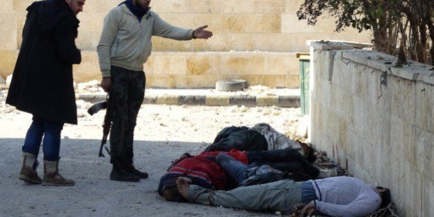 GRAPHIC CONTENTRebel fighters gesture next to the bodies of handcuffed and blindfolded dead men laying...