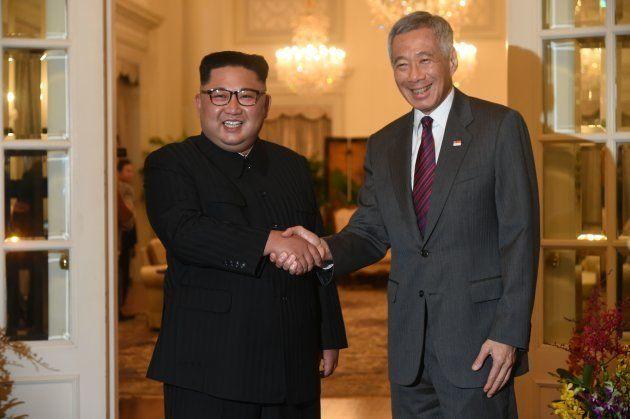 トランプ氏との会談場所であるシンガポールに到着し、同国のリー・シェンロン首相(右)と握手を交わす金正恩氏=6月10日、シンガポール