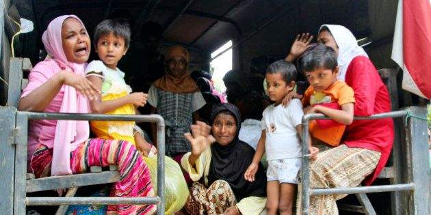 Ethnic Rohingya women and children whose boats were washed ashore on Sumatra Island board a military...