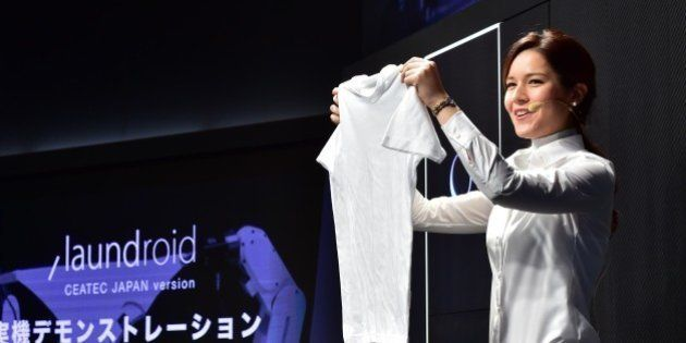 A model demonstrates a prototype of an automatic laundry folding machine during Ceatec, Asia's largest...