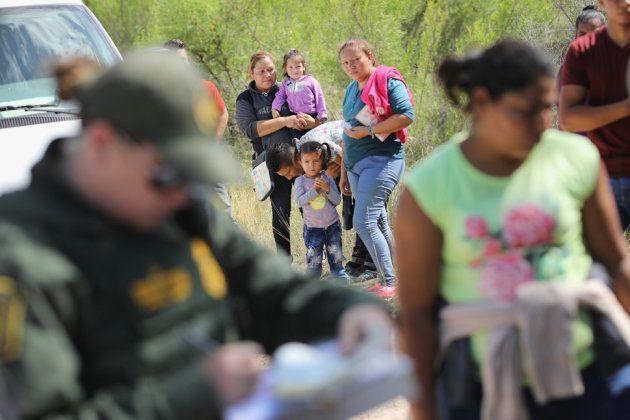 拘束された一家。手続きセンターに連れて行かれた後に、親子は引き離される可能性がある。2018年6月12日、テキサス州マッカレン近くで撮影。