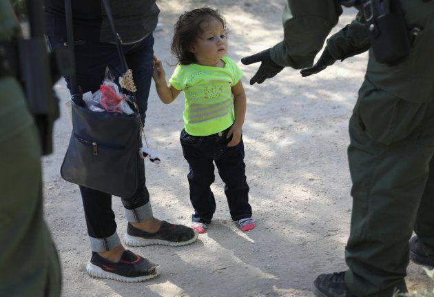 中米からの亡命希望者を拘束する、国境パトロール隊員。2018年6月12日、テキサス州マッカレンで撮影。