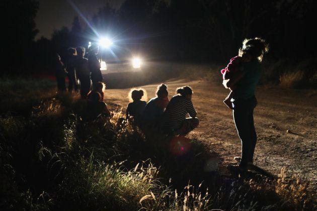 国境パトロールによって拘束された、女性と子供のグループ。彼らはリオ・グランデ川をボートで渡って、アメリカに来た。移民手続きセンターに連れていかれた後、親子は別の場所で拘束される可能性がある。2018年6月12日テキサス州マッカレンで撮影。