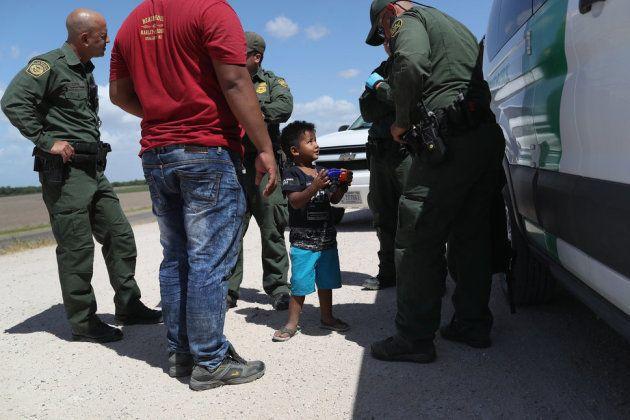 国境近くで拘束される、ホンジュラスから来た男の子と父親。2018年6月12日、テキサス州ミッションで撮影。