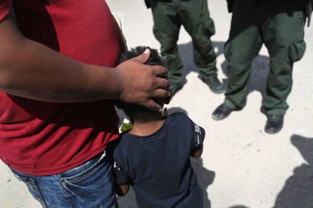 国境パトロールの隊員によって拘束される、ホンジュラス出身の父と息子。2018年6月12日、テキサス州ミッションで撮影。
