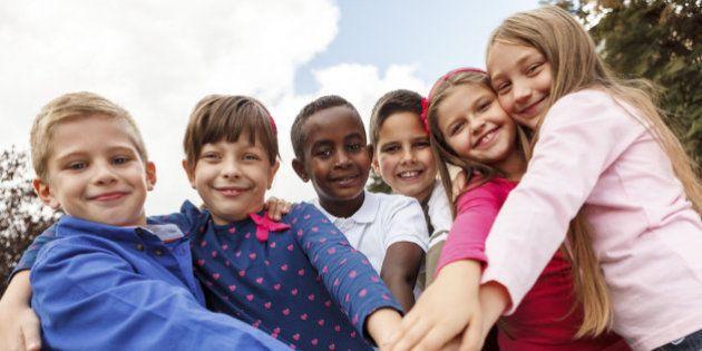 Multiracial school children putting their hands
