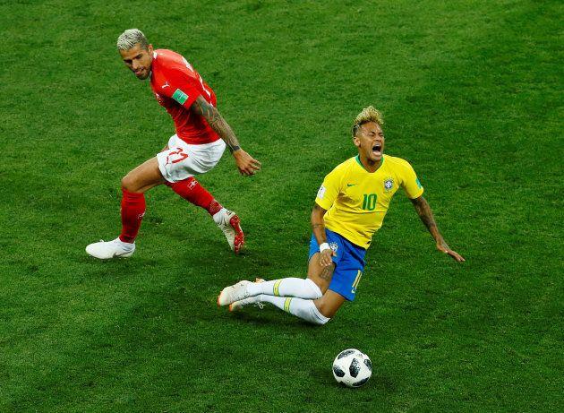 スイスと対戦し、転倒するブラジルのネイマール(右)=6月17日、ロシア・ロストフナダヌー