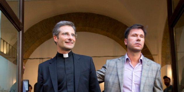 Monsignor Krzysztof Charamsa, left, and his boyfriend Eduard, surname not given, pose for a photo as they leave a restaurant after a news conference in downtown Rome, Saturday Oct. 3, 2015. The Vatican on Saturday fired Charamsa who came out as gay on the eve of a big meeting of the world's bishops to discuss church outreach to gays, divorcees and more traditional Catholic families. (AP Photo/Alessandra Tarantino)