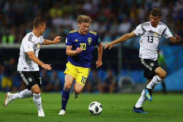 ドイツ選手と競り合うスウェーデンのフォルスベリ(中央)=6月23日、ロシア・ソチ