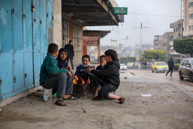 大雨の後の冷え込んだ日、自宅には暖房もなく通りで共に暖を取るガザの子どもたち