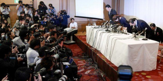 Haruko Obokata (R), 30, a female researcher of Japan's Riken Institute bows as she apologises at a press...
