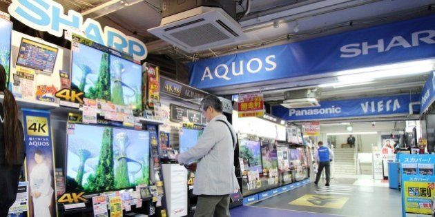 A customer (C) looks at LCD television sets made by Japanese electronics manufacturer Sharp at an electrics...
