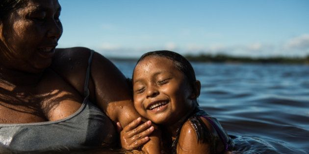 A 4-year-old girl and her mother swim in the Negro river in Manaus, state of Amazonas, Brazil, on November...