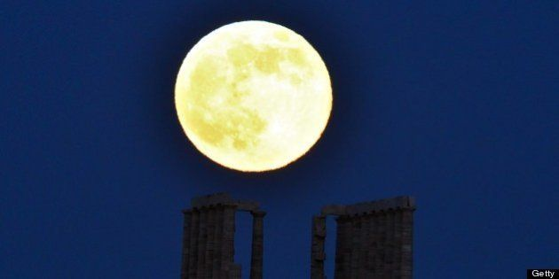 A supermoon rises next to the ancient Greek temple of Poseidon at Cape Sounion, some 65 kilometers south...