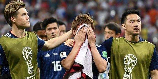 試合終了後、タオルで顔を多いながら泣く乾貴士選手ら=7月2日、ロシア・ロスウトフナドヌー