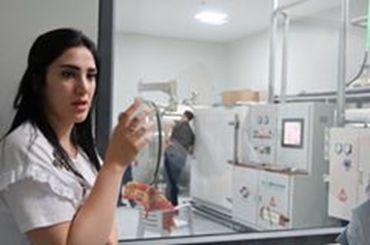 ナツメヤシから糖分を抽出する機械を前に自らのビジネスについて語るタリフィさん