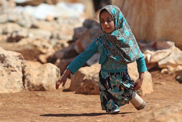 キャンプ内を空き缶の義足で歩くマヤ・メルヒさん=6月20日、シリア・イドリブ